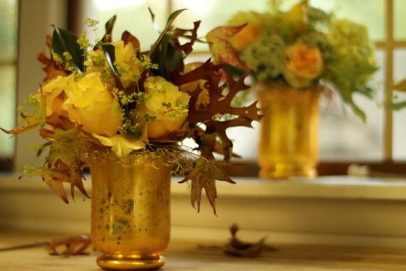 Fall Design using gold hurricane vase with a decorative mesh wire net holding stems in place